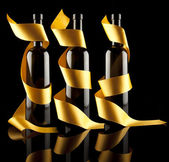 Gold ribbons around bottles — Stock Photo