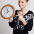 Beautiful girl with a big clock in his hands — Stock Photo