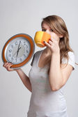 Portrait of a girl with a cup and a clock — Stock Photo