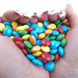 Colored candies in hands — Stock Photo