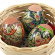 Close-up of three Easter eggs in a wicker basket over a white - Stock Photo