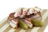 Salted cucumbers and smoked bacon on a hardboard — Stock Photo