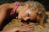 Mujer en traje de baño en una roca en el agua — Foto de Stock