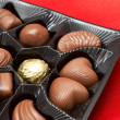 Valentines chocolates in box on red silk — Stock Photo