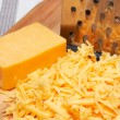Royalty-Free Stock Photo: Grated cheddar cheese on wooden board