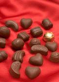 Valentines chocolates on red silk — Stock Photo