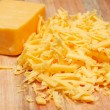 Grated cheddar cheese on wooden board — Stock Photo