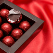 Chocolate Valentines truffles in red paper — Stock Photo