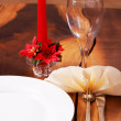 Beautiful table setting with a candle in the background — Stock Photo