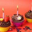 Miniature chocolate cupcakes with candle — Stock Photo