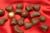 Valentines chocolates on red silk — Stock Photo