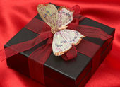 Miláček dar na červené hedvábí — Stock fotografie