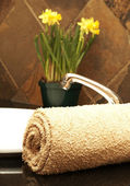Rolled up towel and flowers in the bathroom — Foto de Stock
