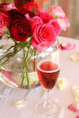 Bouquet of roses and glass of champagne — Stock Photo