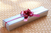 Silver gift box with pink bow — Stock Photo