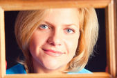 Portrait of the girl in a wooden frame — Stock Photo