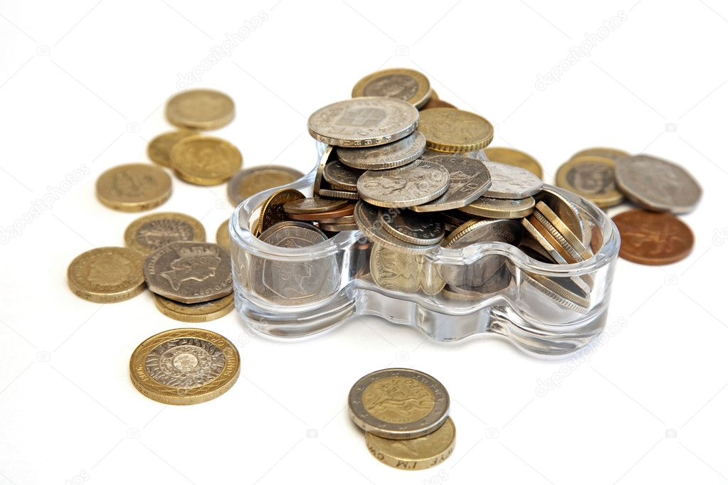 A lot of different coins thrown into the glass vessel  — Stock Photo #5366018