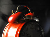 Alarm clock red in the foreground — Stock Photo