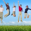 图库照片: Jumping young happy group in meadow