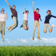 Jumping young happy group in meadow - Stockfoto