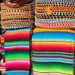 Mexican serape colorful stacked and charro hats - Stock Photo