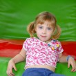 Blond little girl resting on colorful playground - Stok fotoraf