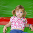 Blond little girl resting on colorful playground - Stockfoto