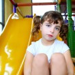 Little girl in colorful playground yellow slide — Stock Photo