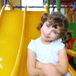 Little girl in colorful playground yellow slide — Стоковая фотография