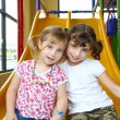 Girls sister friends on playground yellow play slide — Stock Photo