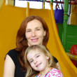 Daughter and mother together in playground slide — Stock Photo