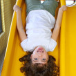 Upside down little girl on playground slide laughing — Stock Photo