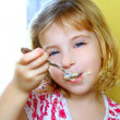 Hungry little blond girl spoon eating ice cream — Stock Photo