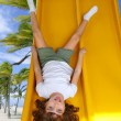 Brunette little girl upside down playground slide — Stock Photo