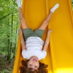 Brunette little girl upside down playground slide — Stock Photo #5125539