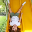 Brunette little girl upside down playground slide — Stock Photo #5125562