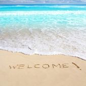 Greetings welcome beach spell written on sand — Stock Photo