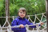 Adventure little girl on jungle park rope bridge — Photo