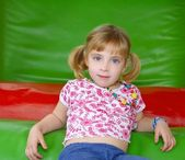Blond little girl resting on colorful playground — Stock Photo