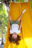 Brunette little girl upside down playground slide — Stock Photo