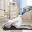 Black mat yoga woman window view city urban buildings - Stock Photo