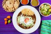 Mole enchiladas mexican food with chili sauces — Stock Photo