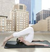 Black mat yoga woman window view city urban buildings — Stock Photo