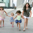 Four little girl group walking in the city — Стоковая фотография