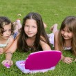 Stock Photo: Three little girl playing with toy computer in grass