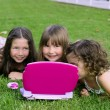 Three little girl playing with toy computer in grass — Stock Photo