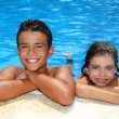 Teen boy and little girl summer vacation in blue pool — Stock Photo #5309420