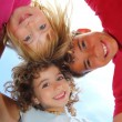 Below view of happy three children embracing - Stockfoto