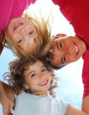 Below view of happy three children embracing — Stock Photo