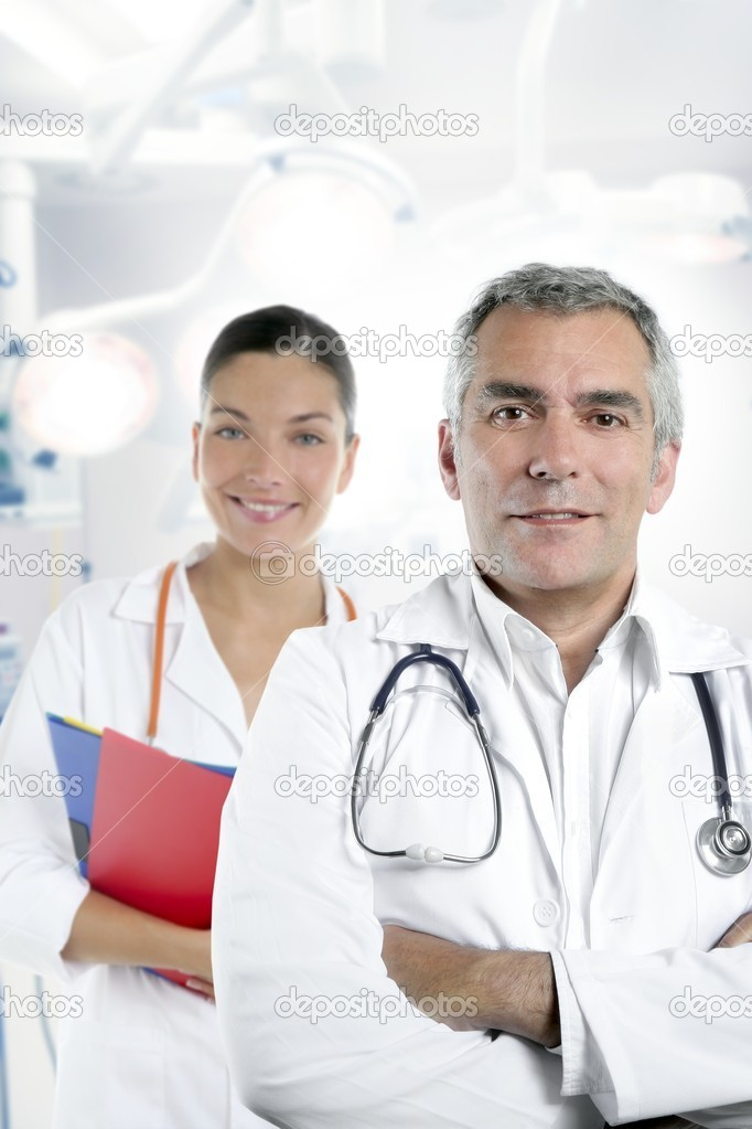 Expertise gray hair doctor beautiful nurse in hospital white corridor — Stock Photo #5309282